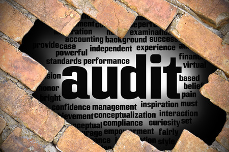 misstatement: Hole at the brick wall with audit word cloud inside. Stock Photo