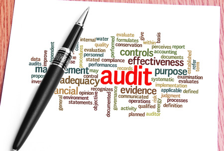 paper, pen and word cloud of audit.