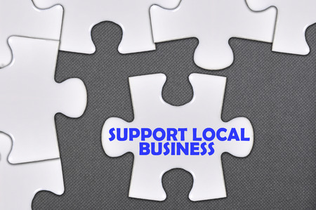 local business: jigsaw puzzle written word support local business. Stock Photo