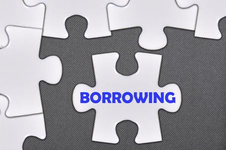 borrowing: jigsaw puzzle written word borrowing . Stock Photo