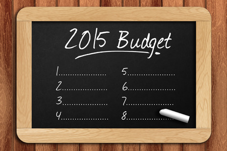 stimulus: Chalkboard on the wooden table written 2015 budget list. Stock Photo