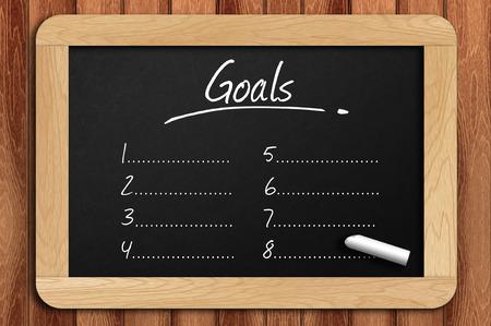 Chalkboard on the wooden table written goals list. Archivio Fotografico