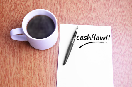 Coffee, pen and notes write cashflow.