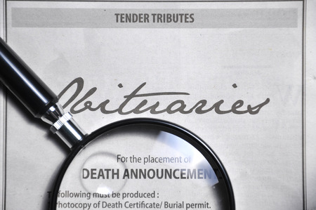 magnifying glass and obituaries advertisement on newspaper.