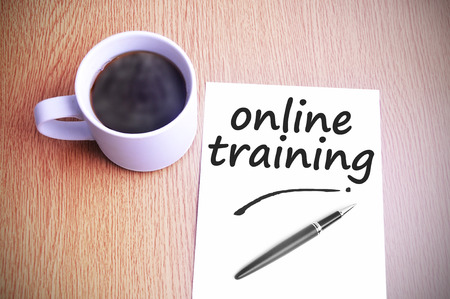 web training: Coffee on the table with note writing online training. Stock Photo