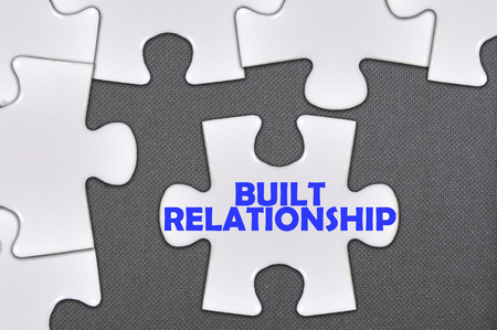 trustful: The white jigsaw puzzle written word built relationship.