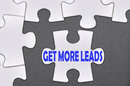 prospecting: The white jigsaw puzzle written word get more leads. Stock Photo