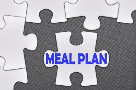 The white jigsaw puzzle written word meal plan. Zdjęcie Seryjne