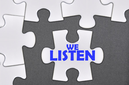The white jigsaw puzzle written word we listen. Stock Photo
