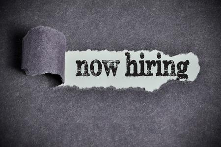 now hiring word under torn black sugar paper. Stock Photo
