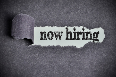 now hiring word under torn black sugar paper. Archivio Fotografico
