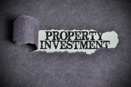 property investment word under torn black sugar paper. Archivio Fotografico