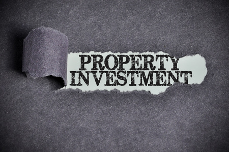 property: property investment word under torn black sugar paper. Stock Photo
