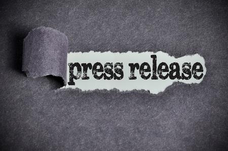 press release word under torn black sugar paper.