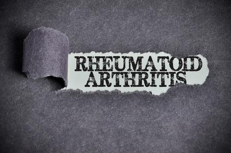eradicate: rheumatoid arthritis word under torn black sugar paper. Stock Photo