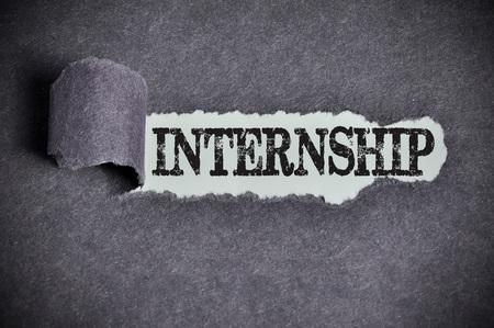 internship: internship word under torn black sugar paper. Stock Photo