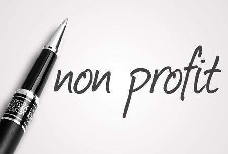 non profit: pen writes non profit on white blank paper.