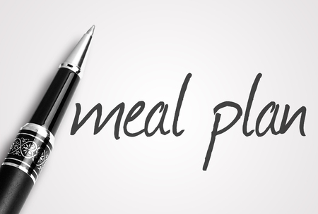 Pióro pisze plan posiłków na białym czystym papierze.