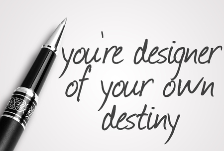 destiny: pen writes youre designer of your own destiny on white blank paper.