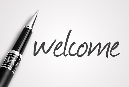 sentiment: pen writes welcome on white blank paper.