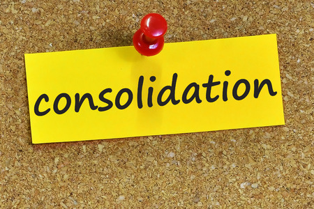 consolidation word on yellow notepaper with cork background. Stock Photo