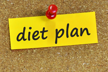 diet plan: diet plan word on yellow notepaper with cork background. Stock Photo