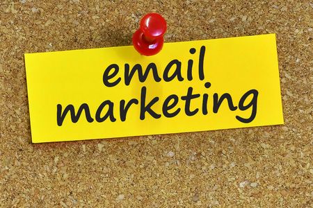 email marketing word on yellow notepaper with cork background. Archivio Fotografico