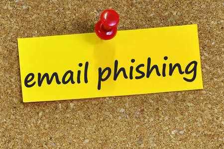 web scam: email phishing word on yellow notepaper with cork background. Stock Photo