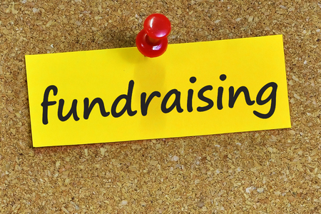 fundraising: fundraising word on yellow notepaper with cork background.