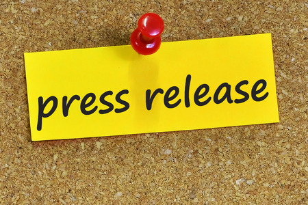press release word on yellow notepaper with cork background.