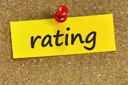 ratings: rating word on yellow notepaper with cork background. Stock Photo