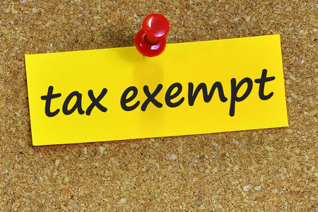 tax exempt word on yellow notepaper with cork background. Stock Photo
