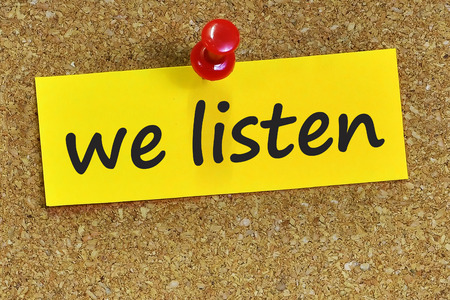 we listen word on yellow notepaper with cork background.