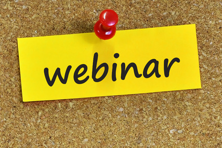 webinar word on yellow notepaper with cork background. Archivio Fotografico