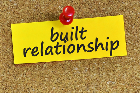 trustful: built relationship word on yellow notepaper with cork background.