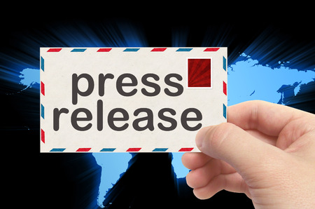 hand press: hand holding envelope with press release word and world background.