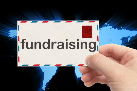 hand holding envelope with fundraising word and world background.