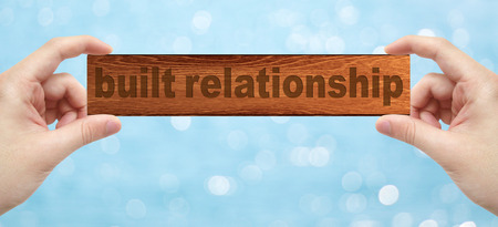 trustful: The Hands holding a wood engrave with word built relationship with bokeh background