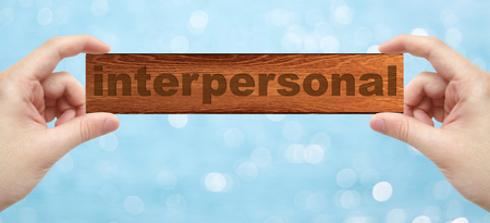 interpersonal: The Hands holding a wood engrave with word interpersonal with bokeh background