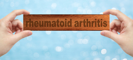 eradicate: The Hands holding a wood engrave with word rheumatoid arthritis with bokeh background Stock Photo