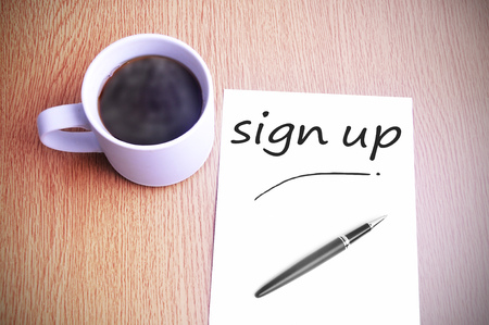 joining services: Black coffee on the table with note writing sign up