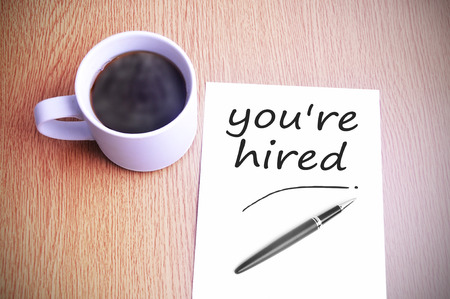 Black coffee on the table with note writing you're hired Archivio Fotografico