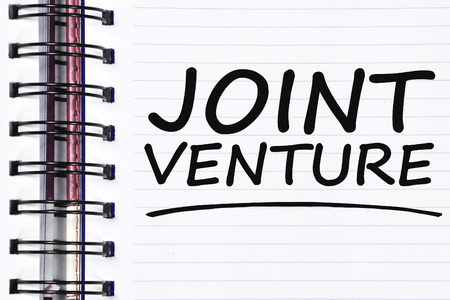 joint venture: joint venture words on spring white note book.