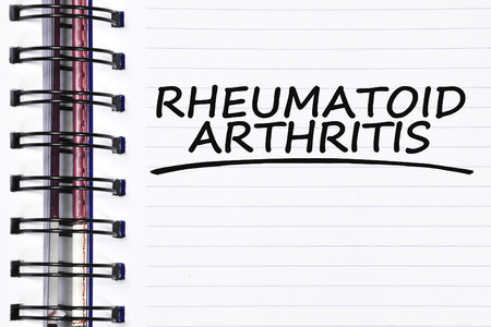 eradicate: rheumatoid arthritis words on spring white note book.