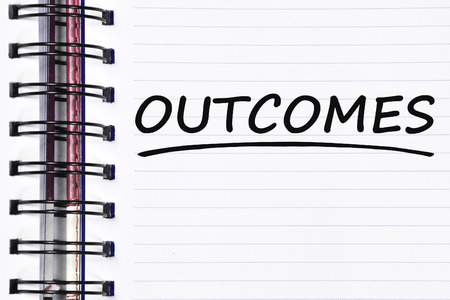 outcomes: outcomes words on spring white note book.