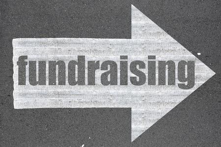 Arrow on asphalt road written word fundraising .