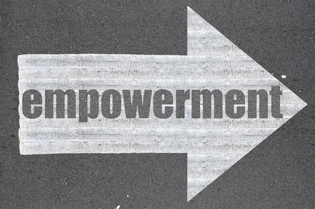 empowered: Arrow on asphalt road written word empowerment .