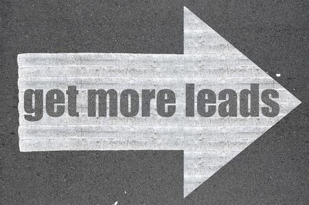 leads: Arrow on asphalt road written word get more leads  .
