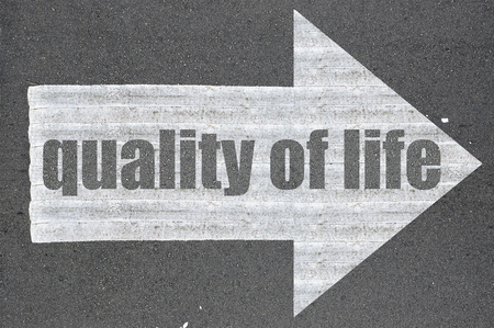zest for life: Arrow on asphalt road written word quality of life . Stock Photo
