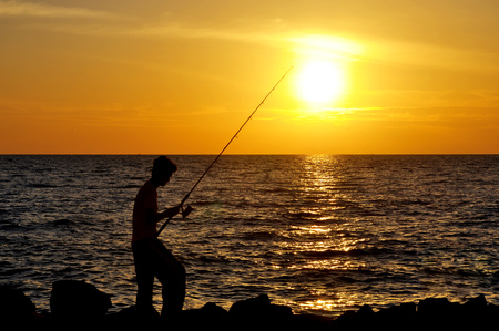 angler: silhouette of angler fishing on the rock at the beach of malacca straits.